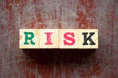 Blocchetto della lettera nel rischio di parola su fondo di legno rosso immagine stock libera da diritti