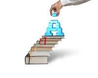 Blocchetto della tenuta della mano che completa i blocchetti della lettera A sulle scale dei libri Immagini Stock
