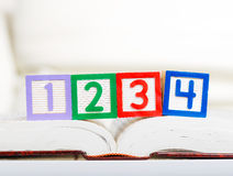 Blocchetto di alfabeto con 1234 sul libro Immagini Stock