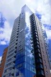 Blocchetto di appartamento in un grattacielo moderno con la riflessione delle nuvole fotografia stock libera da diritti