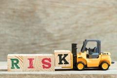 Blocchetto K della lettera della tenuta del carrello elevatore del giocattolo per esprimere rischio su fondo di legno immagine stock libera da diritti