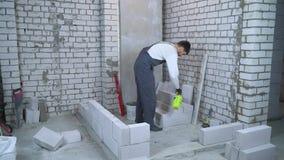 Blocchetto moisturing del giovane costruttore maschio con lo spruzzatore dell'acqua prima della stenditura  archivi video