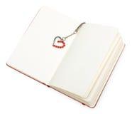 Blocchetto per appunti aperto di colore rosso (documento) con il segnalibro del cuore Immagini Stock Libere da Diritti