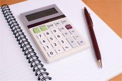 Blocchetto per appunti di piano finanziario con il calcolatore e la penna Fotografia Stock Libera da Diritti