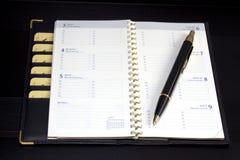 Blocchetto per appunti e penna su priorità bassa nera Fotografia Stock