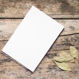 Blocchetto per schizzi bianco in bianco con la foglia di alloro su fondo di legno Fotografia Stock