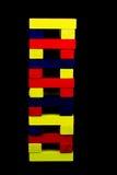 Blocchi di legno colorati impilati contro un fondo nero Fotografia Stock