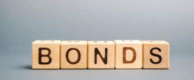 Blocchi di legno con i legami di parola Un legame ? una sicurezza che indica che l'investitore ha fornito un prestito all'emitten immagini stock