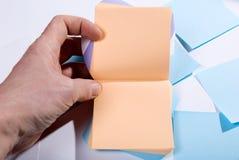 Blocco di note di Post-it. Mano che tiene le pagine in bianco per le note Fotografia Stock