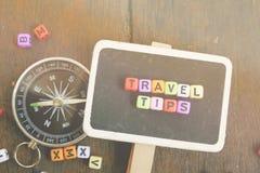 Blocco di parole di viaggio, su fondo di legno con la bussola Immagine Stock Libera da Diritti