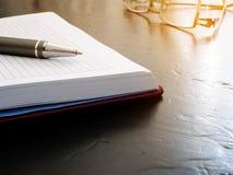 Blocco note aperto con la penna ed i vetri Ricordo sullo scrittorio immagine stock libera da diritti