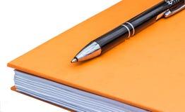 Blocco note arancio con la penna di palla su un fondo bianco Fotografia Stock