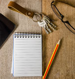 Blocco note in bianco, catena chiave, vetri dell'occhio e telefono cellulare su di legno Fotografie Stock Libere da Diritti