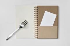 Blocco note in bianco con la forcella e pezzo di carta su fondo bianco Immagine Stock
