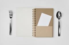 Blocco note in bianco con la forchetta, il cucchiaio e pezzo di carta su fondo bianco Immagine Stock