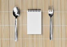 Blocco note in bianco con la forchetta, il cucchiaio e pezzo di carta sul fondo di bambù della stuoia Immagine Stock
