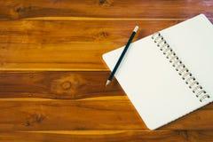 Blocco note in bianco con la matita sulla tavola di legno Fotografia Stock