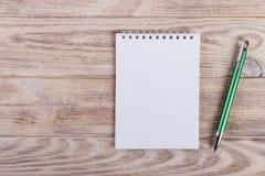Blocco note in bianco con la penna sulla tavola di legno dell'ufficio Fotografie Stock