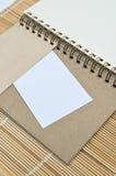 Blocco note in bianco con pezzo di carta sul fondo di bambù della stuoia Fotografia Stock Libera da Diritti