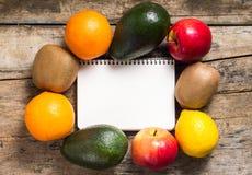 Blocco note in bianco di ricetta con i frutti intorno su fondo di legno Immagini Stock