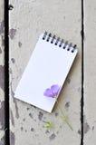 Blocco note in bianco e fiore viola sul fondo rustico di legno della plancia Fotografia Stock Libera da Diritti
