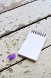 Blocco note in bianco e fiore viola sul fondo rustico di legno della plancia Immagine Stock