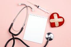 Blocco note in bianco, lo stetoscopio e cuore con cerotto adesivo o Fotografia Stock Libera da Diritti
