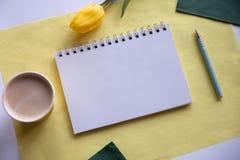 Blocco note in bianco su fondo giallo fotografia stock