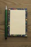 Blocco note colorato e una penna verde su un fondo di legno Fotografie Stock Libere da Diritti