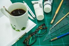 Blocco note con gli oggetti stazionari per materiale illustrativo e caffè caldo Fotografia Stock