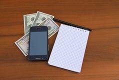 Blocco note con i contanti della penna, dello smartphone e del dollaro sullo scrittorio di legno Immagine Stock