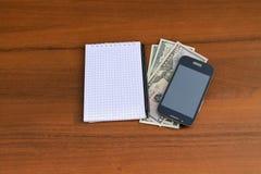 Blocco note con i contanti della penna, dello smartphone e del dollaro sullo scrittorio di legno Immagini Stock Libere da Diritti