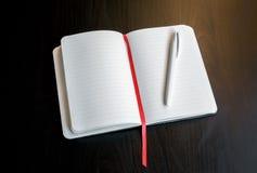 Blocco note con il segnalibro rosso su una tavola scura con una penna Fotografia Stock Libera da Diritti
