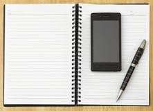 Blocco note con il telefono cellulare Immagini Stock Libere da Diritti