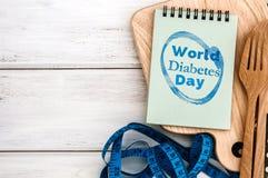Blocco note con il testo di giornata mondiale del diabete sul tagliere con legno Fotografia Stock