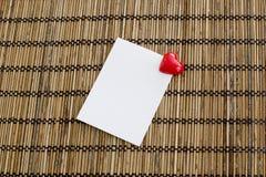 Blocco note con la clip di forma del cuore con colore rosso sul backgrou di legno Immagini Stock Libere da Diritti