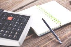 Blocco note con la penna e calcolatore sulla tavola fotografia stock libera da diritti