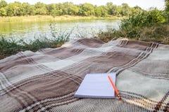 Blocco note, blocco note con la penna e matita, registrare in un parco vicino ai fiumi ed ai laghi, alla spiaggia, caduta di esta fotografia stock libera da diritti