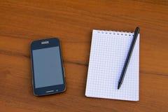 Blocco note con la penna e smartphone sullo scrittorio di legno Fotografia Stock Libera da Diritti