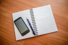 Blocco note con la penna ed il telefono Immagine Stock Libera da Diritti