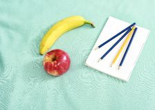 Blocco note con le matite e una certa frutta fresca fotografie stock libere da diritti