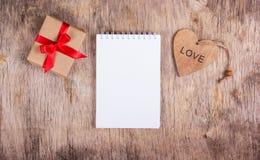 Blocco note con le pagine in bianco e un legno del biglietto di S. Valentino di sorpresa Blocco note con le pagine in bianco e un Immagine Stock