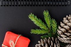 Blocco note, coni, rami attillati e regali - concetto del Natale immagini stock libere da diritti