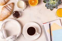 Blocco note, cuffie, croissant e caffè sulla tavola bianca Immagine Stock