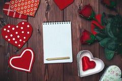 Blocco note, cuori del giocattolo e rose rosse alti falsi aperti sulla tavola di legno romantico immagini stock libere da diritti