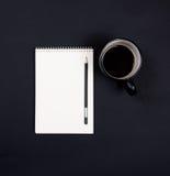 Blocco note del Libro Bianco e una tazza di caffè sulla parte posteriore nera della lavagna Immagini Stock