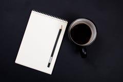 Blocco note del Libro Bianco e una tazza di caffè sulla parte posteriore nera della lavagna Fotografie Stock Libere da Diritti