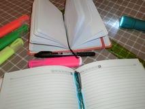 Blocco note del modello, diario con la penna, matita, indicatori e una torcia elettrica Fotografia Stock