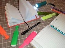 Blocco note del modello, diario con la penna, matita, righello, indicatori e una torcia elettrica Fotografia Stock