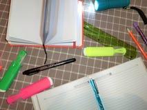Blocco note del modello, diario con la penna, matita, righello, indicatori e una torcia elettrica Immagini Stock